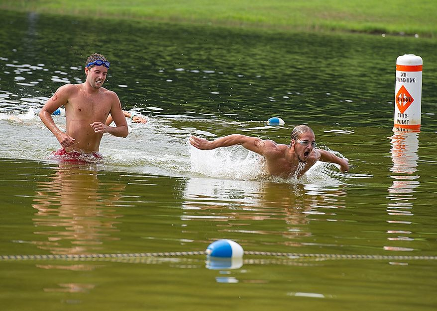Bryce Monges], left, who works at Deep Creek State Park, and Tyler Tasker, who works at Harrington State Park, complete their 300-yard swim as part of the Iron Guard competition, which consists of a 300-yard swim followed by a one-mile run and then another 100-yard swim. This was one of the events in the 23rd annual Lifeguard Competition at Greenbrier State Park in Boonsboro, Md. on Tuesday, Aug. 7, 2012. More than 60 lifeguards who work at state parks across Maryland competed throughout the day. The winners receive a trophy, but most importantly get bragging rights. (Barbara L. Salisbury/The Washington Times)