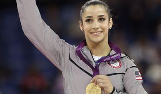 U.S. gymnast Aly Raisman displays her gold medal during the podium ceremony for the artistic gymnastics women's floor exercise final at the 2012 Summer Olympics, Tuesday Aug. 7, 2012, in London. (AP Photo/Gregory Bull)