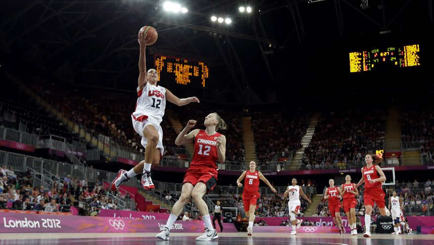 Team USA's Diana Taurasi (left) leaps past Canada defender Lizanne Murphy (12) to score Aug. 7, 2012, during a quarterfinal women's basketball game at the 2012 Summer Olympics in London. (Associated Press)