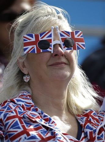 A fan replete with representations of Great Britain's flag watches the competition at the rowing venue in Eton Dorney, near Windsor, England, at the 2012 Summer Olympics in London. (Associated Press)
