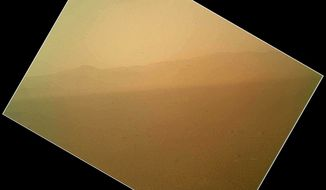 This image released on Aug. 7, 2012, by NASA shows the first color view of the north wall and rim of Gale Crater where NASA's rover Curiosity landed two days prior. The picture was taken by the rover's camera at the end of its stowed robotic arm and appears fuzzy because of dust on the camera's cover. (Associated Press/NASA)
