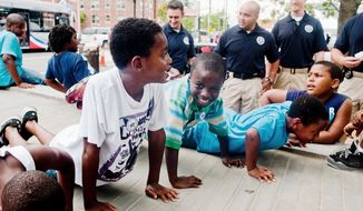 Mailk Brooks, 10 , Jeremiah Mikell, 9, and Devin Waters, 9, all from Washington D.C., do push ups for U.S. Marshals during the Seven District's National Night Out.  (Raymond Thompson/The Washington Times)