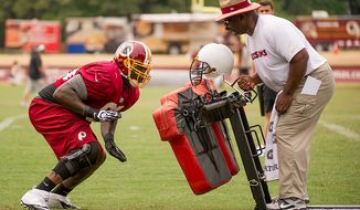 ** FILE ** Washington Redskins defensive tackle Jarvis Jenkins (99), left, works with Washington Redskins defensive line coach Jacob Burney  during afternoon practice at training camp at Redskins Park, Ashburn, Va., Tuesday, August 7, 2012. (Andrew Harnik/The Washington Times)