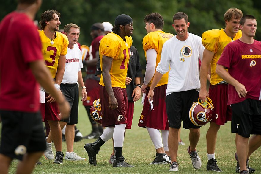 The Washington Redskins quarterbacks walk off the field at the conclusion of afternoon practice at training camp at Redskins Park, Ashburn, Va., Tuesday, August 7, 2012. (Andrew Harnik/The Washington Times)