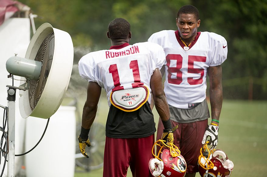Washington Redskins wide receiver Aldrick Robinson (11), left, and Washington Redskins wide receiver Leonard Hankerson (85), right, cool off in front of misting fans following afternoon practice at training camp at Redskins Park, Ashburn, Va., Tuesday, August 7, 2012. (Andrew Harnik/The Washington Times)