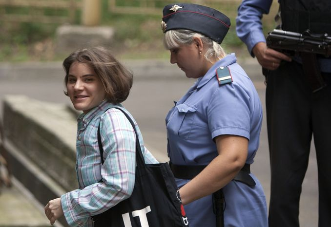"""Yekaterina Samutsevich (left), a member of feminist punk group Pussy Riot, is escorted Aug. 7, 2012, to a courtroom in Moscow. Samutsevich and two other members of the group are facing trial on charges of hooliganism for performing a """"punk prayer"""" at Moscow's main cathedral against Vladimir Putin's return to the Russian presidency. (Associated Press)"""