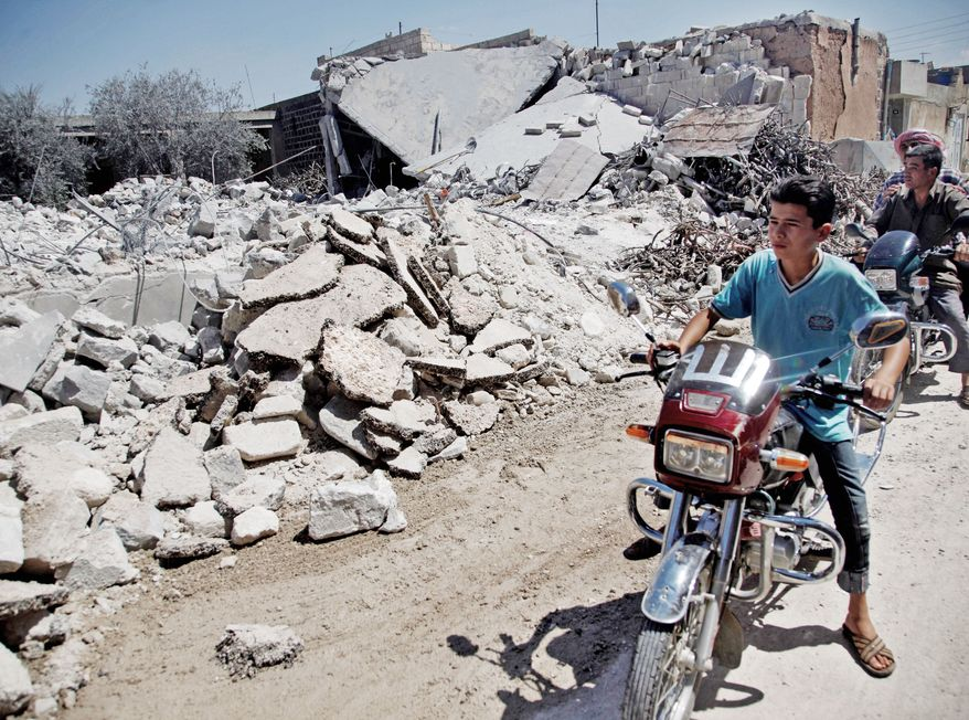 Syrians on motorcycles inspect the damage of a destroyed house in the town of Tal Rifat on the outskirts of Aleppo, Syria, on Wednesday. Syrian fighter jets carried out airstrikes on the village, hitting a home and a high school, and killing six people from the same family. It was unclear why the area was targeted. (Associated Press)