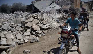 Syrians on motorcycles look Aug. 8, 2012, at the damage of a destroyed house after it was hit by an airstrike that killed six Syrians in the town of Tal Rifat, Syria. (Associated Press)