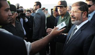 Egyptian President Mohammed Morsi (right) speaks to the media as Field Marshal Gen. Hussein Tantawi (second from right) listens during their visit to El Arish, in Egypt's northern Sinai Peninsula, on Sunday, Aug. 5, 2012.  (AP Photo/Egyptian Presidency)