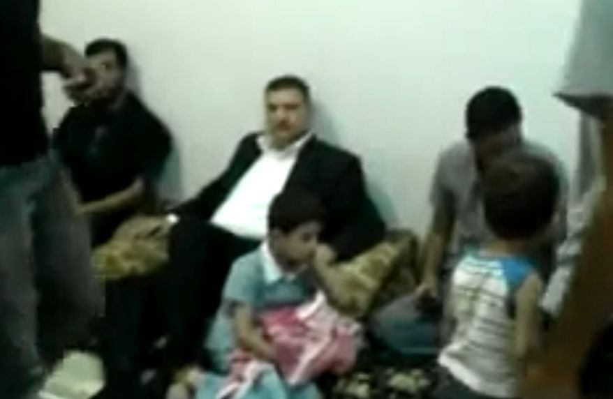 This image made from amateur video released by the Shaam News Network and accessed Aug. 7, 2012, purports to show defected Prime Minister Riad Hijab (center) before leaving Syria en route to Jordan in Daraa, Syria. (Associated Press/Shaam News Network via AP video)