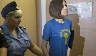 Feminist punk group Pussy Riot member Nadezhda Tolokonnikova is escorted Aug. 8, 2012, at a court in Moscow. Tolokonnikova and two other group members have been in custody for five months after giving an impromptu performance in Moscow's main cathedral to call for an end to Vladimir Putin's rule. (Associated Press)