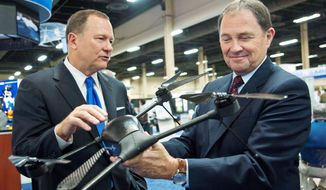 Lockheed Martin Vice President for Ship and Aviation Systems Dan Schultz (left) shows a mini unmanned aerial vehicle, the Quad Vertical Take Off and Landing System, to Utah Gov. Gary R. Herbert at the Association for Unmanned Vehicle Systems International convention in Las Vegas on Wednesday. (Martin S. Fuentes/Special to The Washington Times)