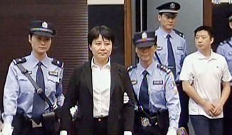 Gu Kailai (second left), the wife of disgraced politician Bo Xilai, is escorted into the Intermediate People's Court in the city of Hefei on Thursday. According to testimony Thursday in the murder trial, Gu lured British businessman Neil Heywood (left) to a hotel in the southwestern mega-city of Chongqing, where she got him drunk and fed him poison. (Associated Press)
