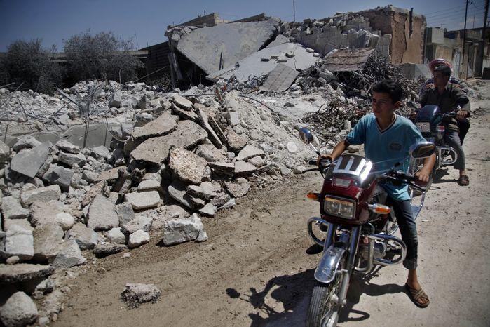 Syrians on motorcycles look at the rubble of a destroyed house after it was hit by an airstrike that killed six people in the town of Tal Rifat, on the outskirts of Aleppo, Syria, on Wednesday, Aug. 8, 2012. (AP Photo/Khalil Hamra)