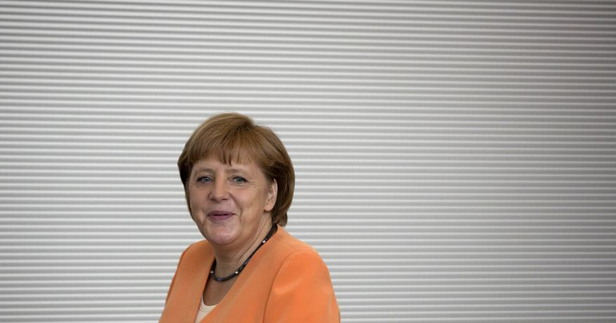 German Chancellor Angela Merkel arrives for a meeting of the CDU/CSU parliamentary parties prior to a special session of the German parliament in Berlin on Thursday, July 19, 2012. (AP Photo/Gero Breloer)