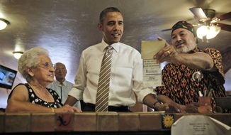 President Obama is shown an old photograph Aug. 9, 2012, at Romero's Cafe and Catering in Pueblo, Colo., by Robert Romero (right), the establishment's owner, and Virginia Romero (left), who founded the establishment. (Associated Press)