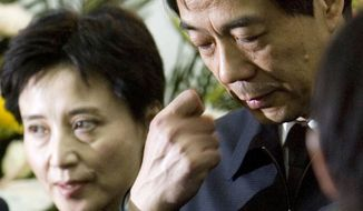 **FILE** Former Chongqing Communist Party Secretary Bo Xilai (right), accompanied by his wife Gu Kailai, attends a funeral for his father in Beijing on Jan. 17, 2007. (Associated Press)