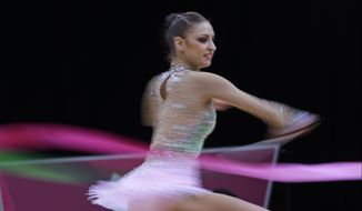 Russia's Evgeniya Kanaeva performs during the rhythmic gymnastics individual all-around qualifications  at the 2012 Summer Olympics, Friday, Aug. 10, 2012, in London. (AP Photo/Julie Jacobson)