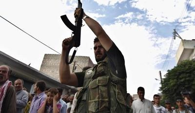 A Syrian gunman shoots into the air Aug. 9, 2012, during the funeral of Free Syrian Army fighter Husain Al-Ali, 29, in the town of Marea on the outskirts of Aleppo city, Syria. The fighter was killed during clashes in Aleppo. (Associated Press)