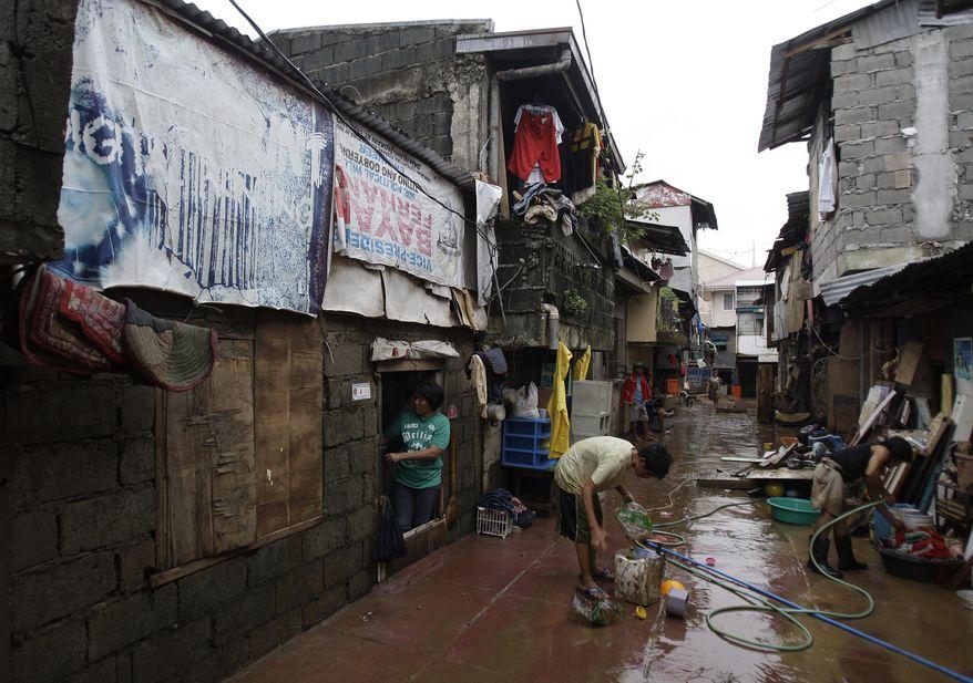 Luzviminda Limas (left) checks her house after floods recede in suburban Marikina city, east of Manila, Philippines on Aug. 10, 2012. (Associated Press)