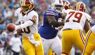 Washington Redskins' Robert Griffin III hands off during the first half of a preseason NFL football game against the Buffalo Bills in Orchard Park, N.Y., Thursday, Aug. 9, 2012. (AP Photo/Bill Wippert)