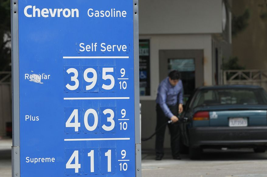 **FILE** A man pumps gas at a Chevron gas station in San Francisco on Aug. 7, 2012. (Associated Press)