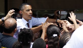 **FILE** President Obama greets people Aug. 2, 2012, outside Lechonera El Barrio, a local restaurant in Orlando, Fla. Obama won the 2008 election with 66% of the Hispanic vote and, according to polls, his popularity among the crucial voting bloc remains the same. (Associated Press)