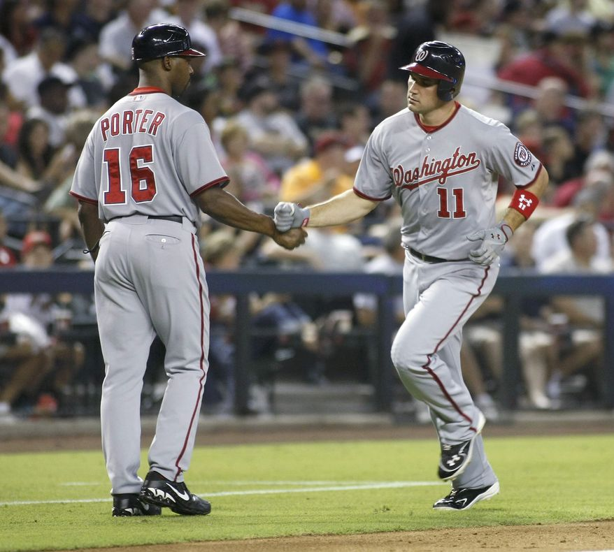 Washington Nationals' Ryan Zimmerman (11) is congratulated by third base coach Bo Porter (16) following his two-run home run off of Arizona Diamondbacks pitcher Trevor Cahill during the fifth inning of a baseball game Friday, Aug. 10, 2012, in Phoenix. (AP Photo/Ralph Freso)