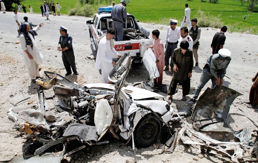 Afghans inspect the wreckage of a vehicle after a roadside explosion on the outskirts of Laghman province east of Kabul, Afghanistan, on Sunday. The bomb killed a district chief and three of his bodyguards. (Associated Press)