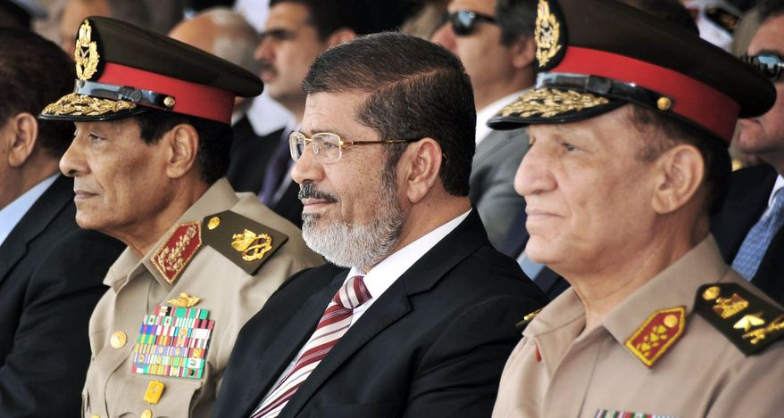 Egyptian Defense Minister Field Marshal Hussein Tantawi (left), President Mohammed Morsi (center) and Armed Forces Chief of Staff Gen. Sami Annan attend a medal ceremony at a military base east of Cairo last month. The president ordered the retirement of the defense minister and chief of staff on Sunday. (Associated Press)