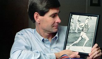 At his home in Lawrence, Kan., in 1991, former Olympian Jim Ryun takes a look at a photograph taken of him at the Olympics in Mexico City in 1968, where he won a silver medal in the 1,500-meter run. On July 21, 2020, Mr. Ryun was named by President Trump as the latest civilian to receive the Medal of Freedom. He will be awarded the honor at a ceremony on Friday, July 24. (Associated Press)  **FILE**