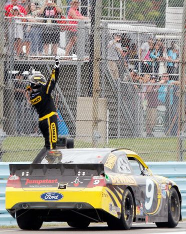 Marcos Ambrose passed Brad Keselowski heading to the final turn in winning the Sprint Cup race at Watkins Glen International for the second straight time. (Associated Press)