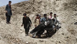 Afghans push parts of a damaged vehicle off a hill after a roadside explosion on the outskirts of Laghman province, east of Kabul, Afghanistan, on Sunday, Aug. 12, 2012. A provincial spokesman said a roadside bomb killed a district chief in eastern Afghanistan and three of his bodyguards. (AP Photo/Rahmat Gul)