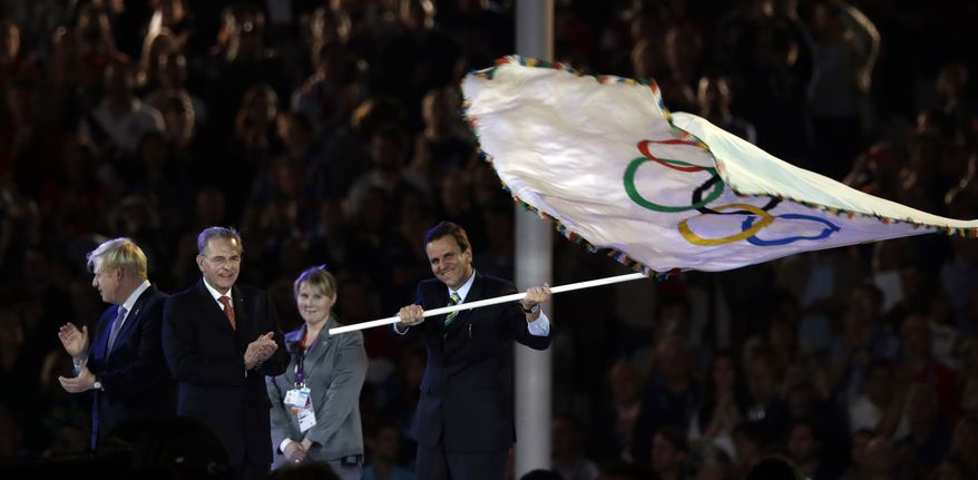Rio de Janeiro mayor Eduardo Paes waves the olympic flag next to Jacques Rogge and London Mayor Boris Johnson, left, during the Closing Ceremony at the 2012 Summer Olympics, Sunday, Aug. 12, 2012, in London. (AP Photo/Charlie Riedel)