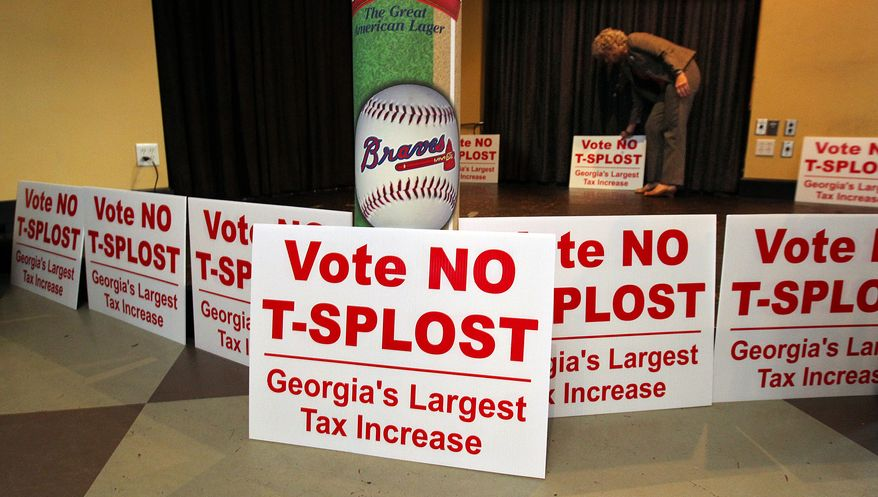 Debbie Dooley, co-founder of the Atlanta Tea Party, sets out signs and waits for returns as groups opposing a proposed sales tax increase that would have raised billions of dollars for transportation projects gather for a election night watch at Hudson Grille in Atlanta on Tuesday, July 31, 2012. (AP Photo/Atlanta Journal-Constitution, Curtis Compton)