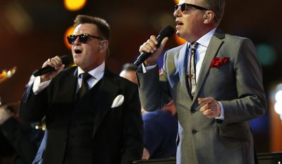 Graham McPherson, also known as Suggs, right, lead singer of British band Madness performs during the Closing Ceremony at the 2012 Summer Olympics, Sunday, Aug. 12, 2012, in London. (AP Photo/Matt Dunham)