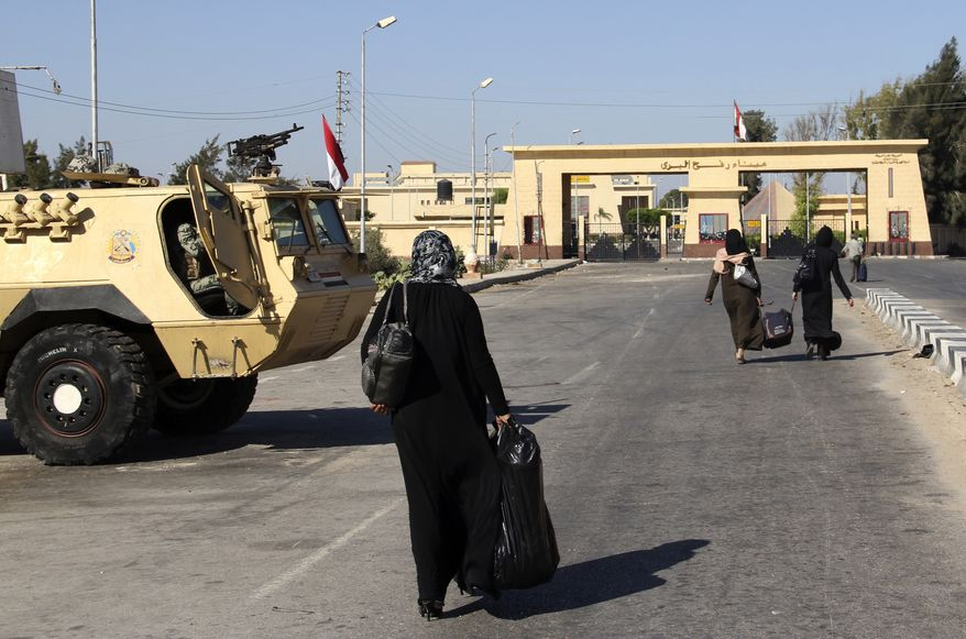 Palestinians walk toward the Egyptian border crossing with Gaza, which temporarily has been reopened but only to allow the passage of Palestinians back to Gaza, in Rafah, Egypt, on Friday Aug. 10, 2012. (AP Photo)