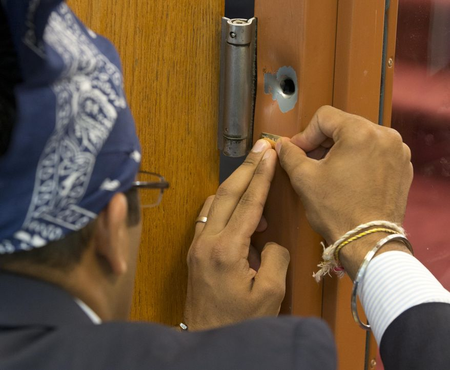 A bullet hole on a door frame has been left in remembrance of those who died in a shooting at the Sikh Temple of Wisconsin in Oak Creek, Wis., on Sunday, Aug. 5, 2012. (AP Photo/Jeffrey Phelps)