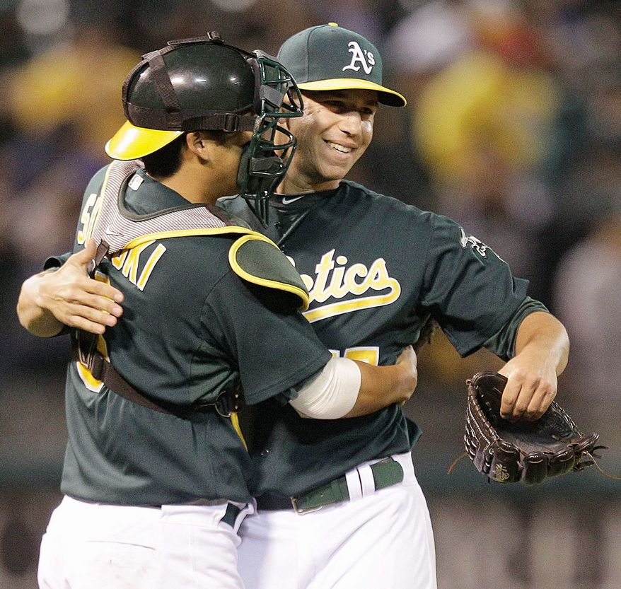While with Oakland, Kurt Suzuki congratulated Tommy Milone, a former Nationals pitcher who was sent to the Athletics in December in the Gio Gonzalez trade. Suzuki was acquired from Oakland on Aug. 3. (Associated Press)