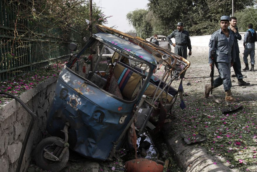 Afghan police officers inspect the scene Aug. 13, 2012, after a bomb explosion in the city of Jalalabad east of Kabul, Afghanistan. (Associated Press)