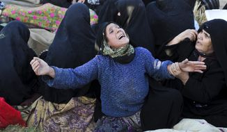 On Sunday, Aug. 12, 2012, an Iranian woman grieves for loved ones who were killed in Saturday's earthquake in the village of Bajebaj in northwestern Iran. (AP Photo/ISNA, Arash Khamoushi)