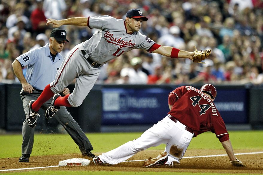 Washington Nationals' Ryan Zimmerman (11) cannot catch the throw as Arizona Diamondbacks' Paul Goldschmidt (44) steals third base during the second inning of a baseball game, Sunday, Aug. 12, 2012, in Phoenix. (AP Photo/Matt York)