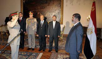 Egyptian President Mohammed Morsi (right) swears in newly-appointed Minister of Defense, Lt. Gen. Abdel-Fattah el-Sissi (left), in Cairo on Aug. 12, 2012. (Associated Press/Egyptian presidency)