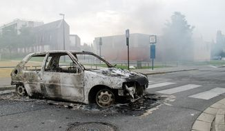 The shell of a car burns out in a neighborhood of Amiens, France, on Tuesday. Dozens of young men rioted in a troubled district in northern France after weeks of tensions. They stole vehicles, and burned a school and a youth center. The police department in Amiens says at least 16 officers were hurt by the time the riot ended Tuesday, some by buckshot. (Associated Press)