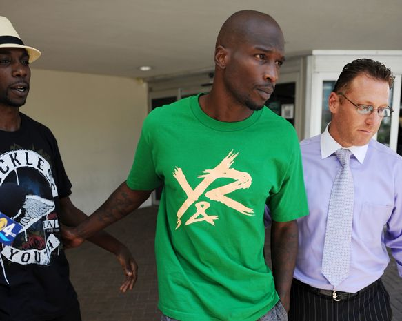 In this Aug. 12, 2012 photo, Chad Johnson, center, leaves Broward County Jail in Fort Lauderdale, Fla. The Dolphins terminated the six-time Pro Bowl receiver's contract about 24 hours after he was arrested in a domestic battery case involving his wife.  Johnson was released from jail on $2,500 bond after his wife accused him of head-butting her during an argument in front of their home. (Photo by Jeff Daly/Invision/AP)