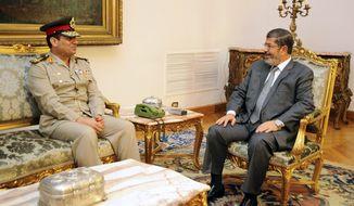 Newly-appointed Egyptian Minister of Defense, Lt. Gen. Abdel-Fattah el-Sissi, left, meets with Egyptian President Mohammed Morsi in Cairo, Egypt, Monday, Aug. 13, 2012. (AP Photo/Egyptian Presidency)