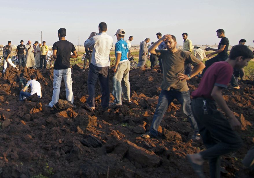 Syrians inspect a hole allegedly made during an airstrike by government forces in the town of Marea, some 21 miles north of Aleppo, Syria, on Monday, Aug. 13, 2012. (AP Photo/ Khalil Hamra)