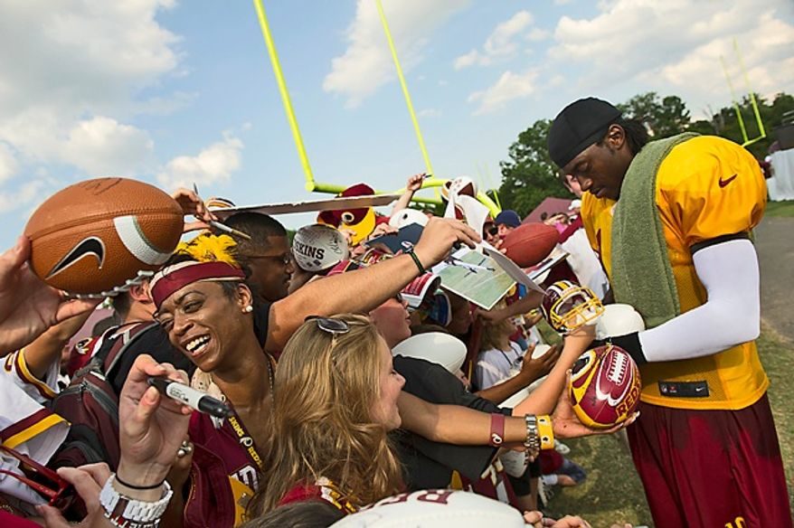Fans line up with souvenirs to get autographs from Redskins quarterback Robert Griffin III (right) on Aug. 13, 2012, following the team's training camp at Redskins Park in Ashburn, Va. (Rod Lamkey Jr./The Washington Times)
