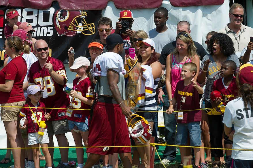 Redskins wide receiver Santana Moss is greeted by fans as he makes his way to the practice field during the Redskins training camp at Redskins Park in Ashburn, Va., Monday, August 13, 2012.  (Rod Lamkey Jr./The Washington Times)