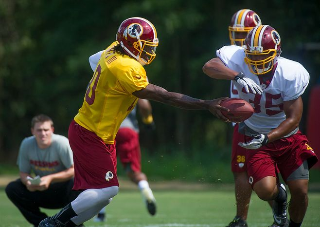 Redskins quarterback Robert Griffin III  hands the ball off to Evan Royster (35) during the Redskins training camp at Redskins Park in Ashburn, Va., Monday, August 13, 2012.  (Rod Lamkey Jr./The Washington Times)